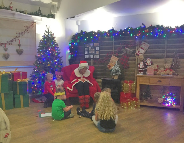afternoon tea with Santa, children sitting around Christmas tree with Mrs Claus