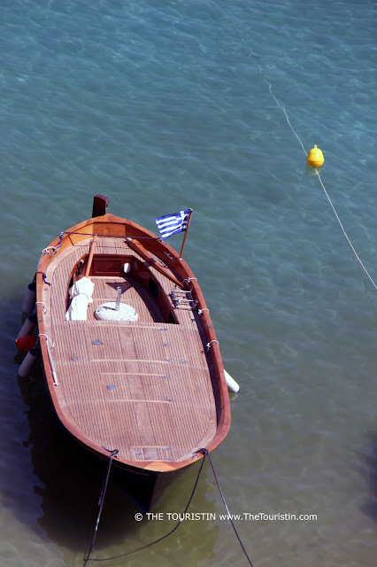A wooden boat with a Greek flag, in the sea.