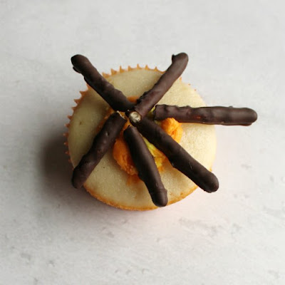 cupcake with dollop of frosting in center and chocolate dipped pretzel sticks fanned around