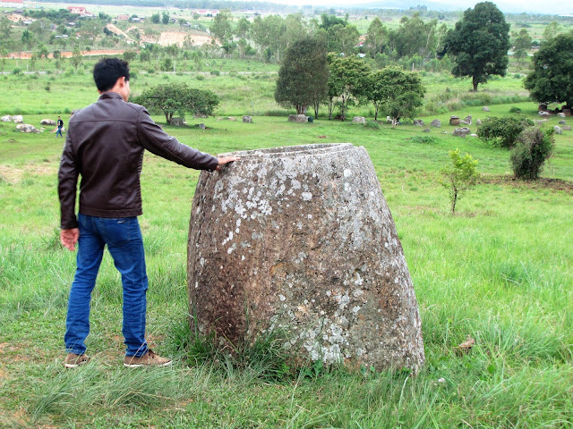 man standing jar plain of jars laos