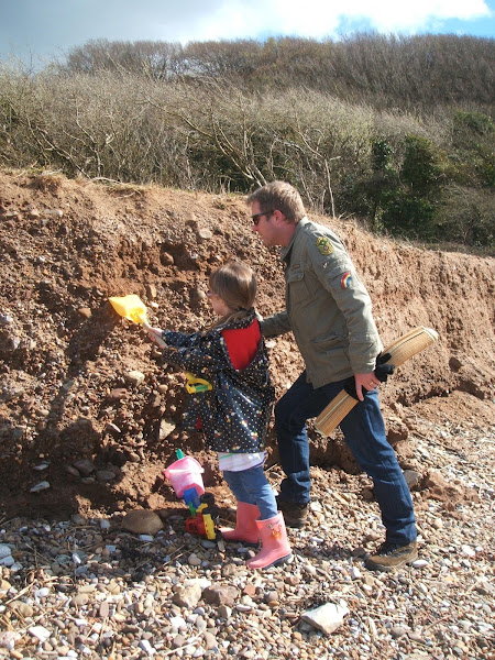 child and father search for pebbles and fossils in sandbanks