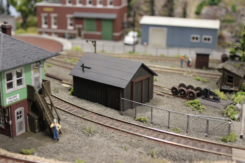 Train maintenance shed and Atlas Signal Tower kit with chain link fence in a railroad maintenance yard