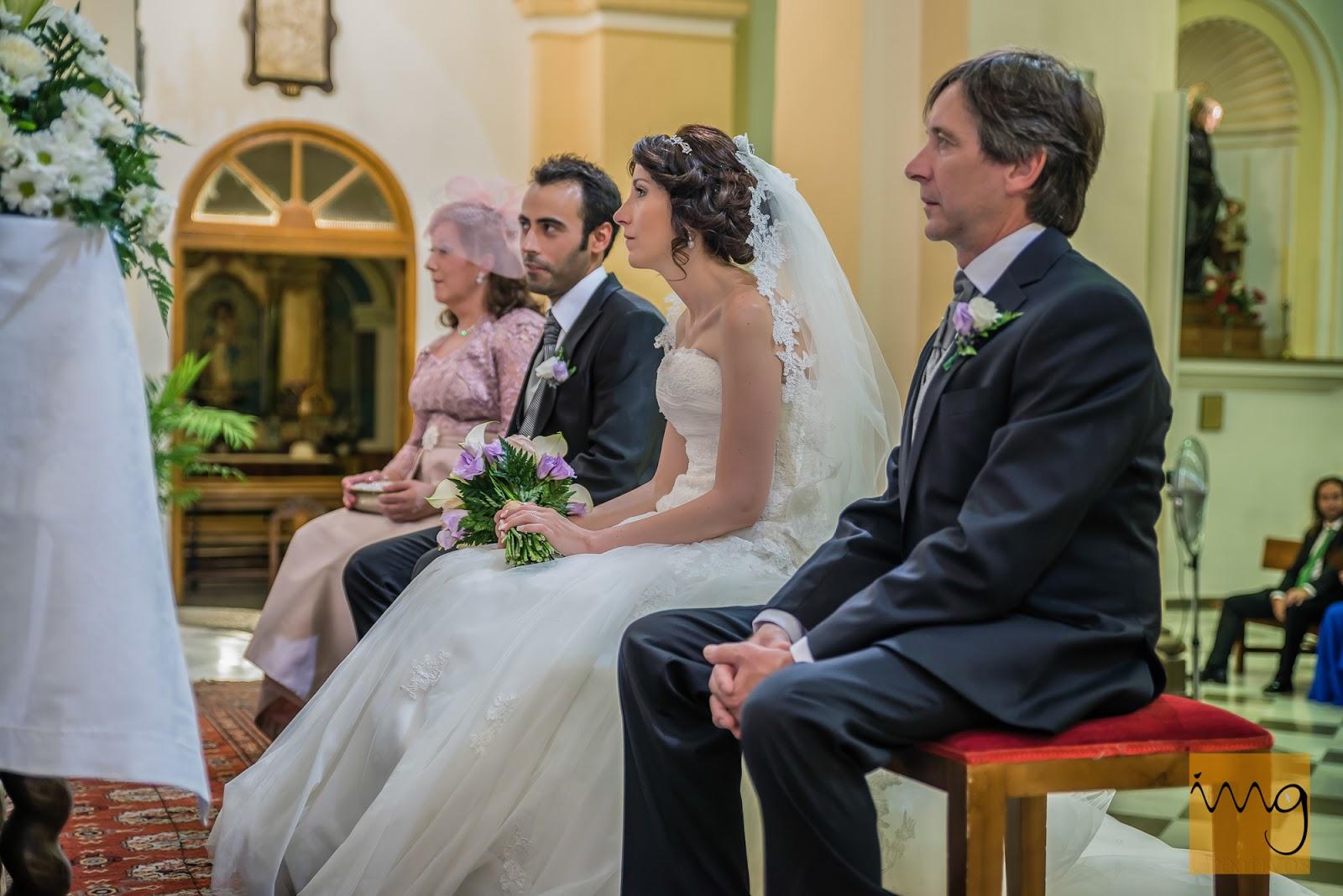 Los novios sentados ante el altar.