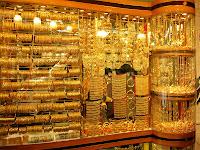 Vitrininde birçok altın bilezik ve kolye asılı olan kuyumcu dükkanı