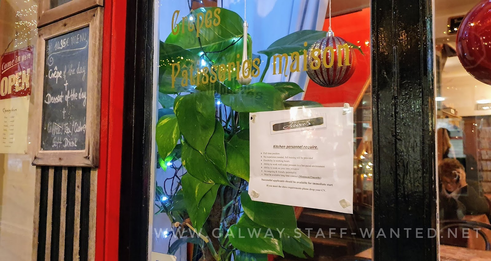 French bistro-style cafe shop window with leafy green plant inside. and a blackboard menu outside