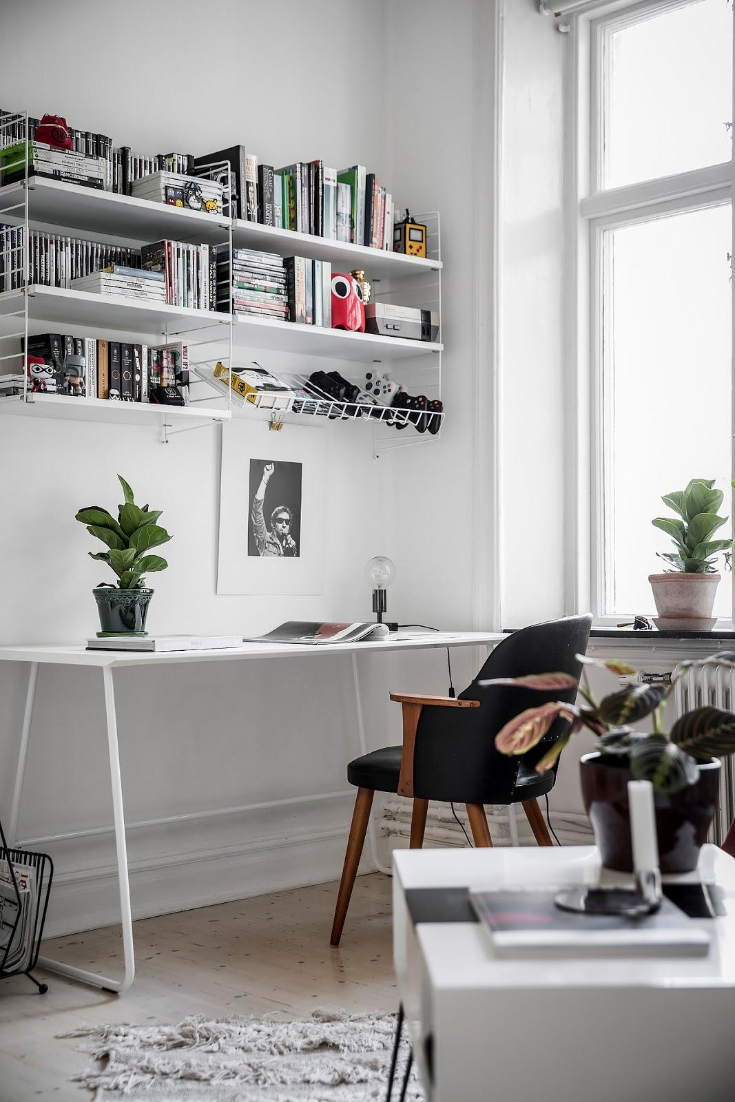 White scandinavian apartment with nice wall art, danish modern chest and IKEA sofa