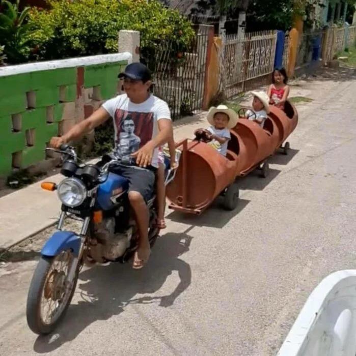 Papá improvisa trenecito con botes de metal para sus hijos