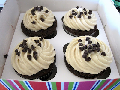 4 chocolate and peanut butter cupcakes in a cupcake box.