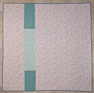 The quilt back is blue pine trees printed on white with a single stripe of blue fabric to add interest