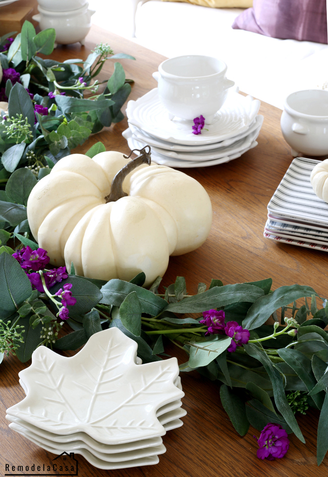 White pumpkins and eucalyptus garland on table