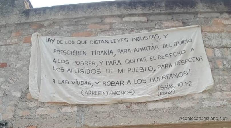 Letrero con versículo de Isaías colgado en fachada de casa