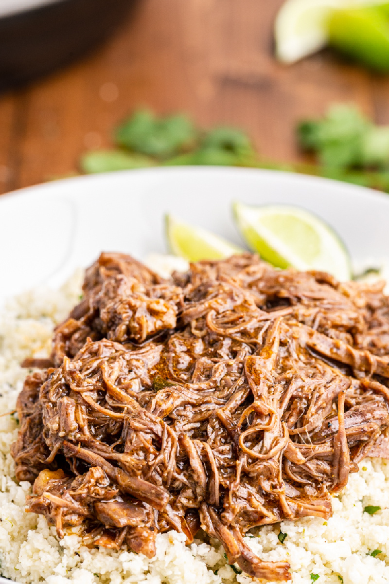 Closeup photo of Instant Pot Mexican Shredded Beef  (Keto, Paleo, Gluten-free) in white bowl with cilantro lime cauliflower rice and lime wedges.