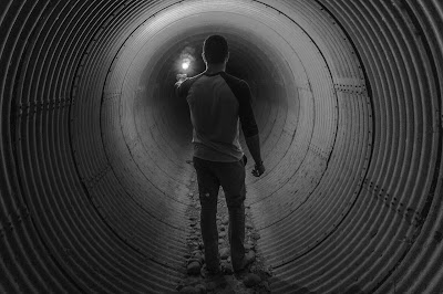 person walking through a dark tunnel