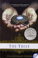 The cover of the book, The Thief shows an amulet in a pair of hands