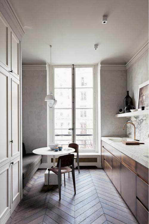 Die Küche mit Parket, hellgrau gestrichen Wänden, bronzefarbener Küchenzeile und einer Arbeitsplatte aus Marmor