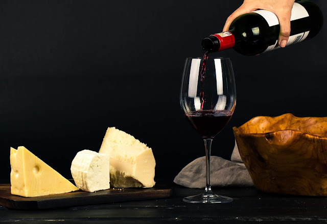 Cheese and wine being poured into a glass