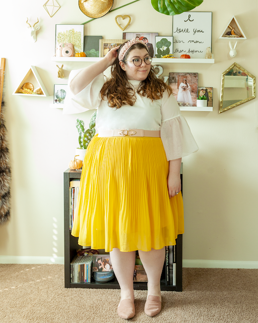 An outfit consisting of a pastel pink headband with white pearls, a white blouse with 3/4 sheer poofy sleeves tucked into a yellow pleated midi skirt belted with a pink belt and muted pink pointed toe mules.