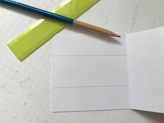 A green ruler and pencil with an open white square card and two pencil lines on the card