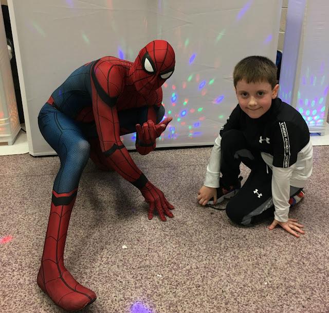 little boy and spiderman kneeling on the floor
