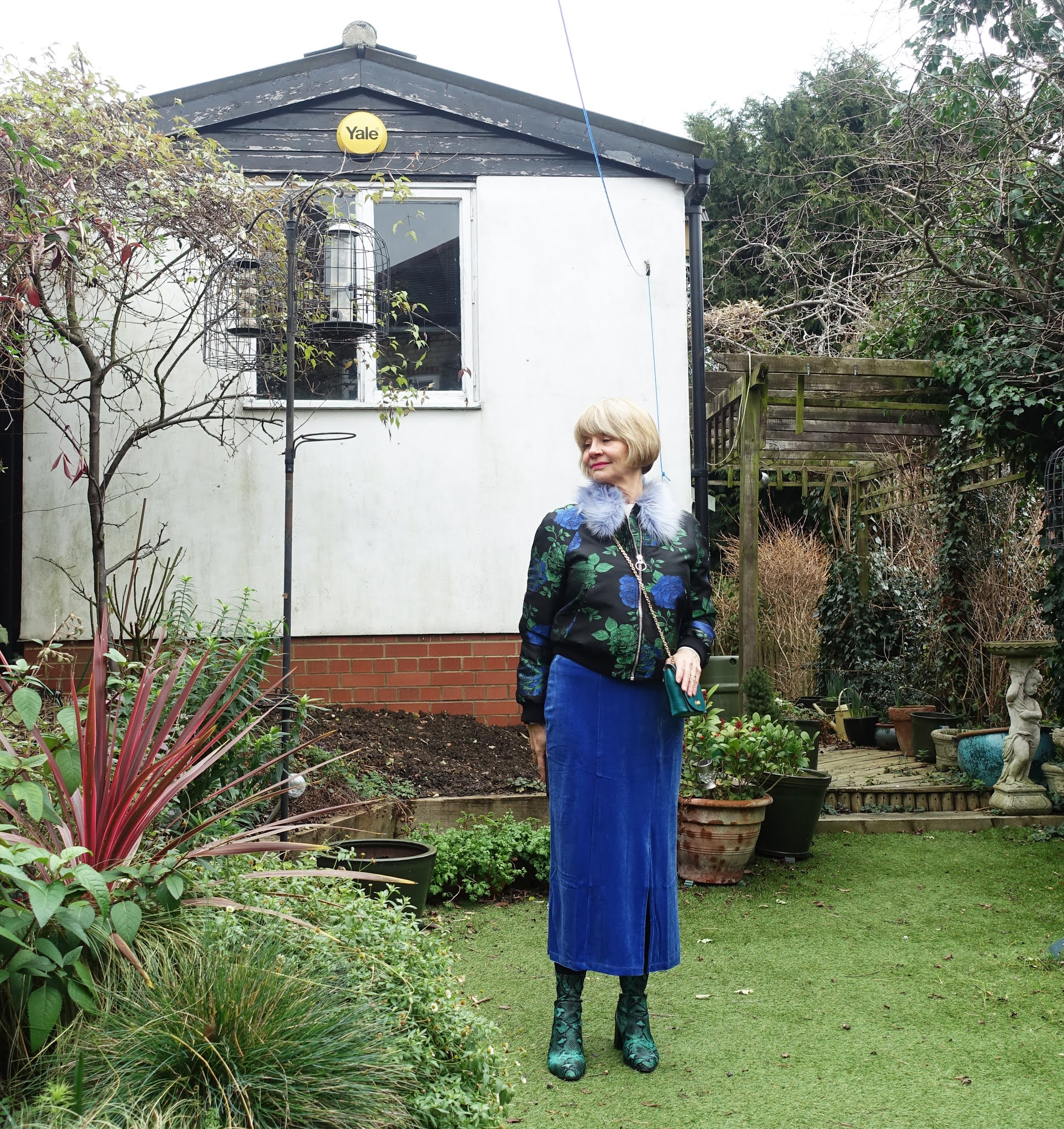 A fur collar brocade jacket in green and blue is paired with a blue velvet skirt and green snakeskin boots for style blogger Gail Hanlon from Is This Mutton