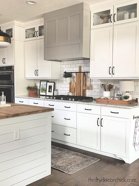 White kitchen gray island black brass accents