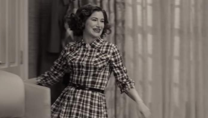 Imagem: a personagem de Kathryn Hahn, Agnes, em uma roupa de época, um vestido quadriculado e um cabelo curto e enrolado saindo por uma porta da frente da sala sorrindo e de forma bem teatral.
