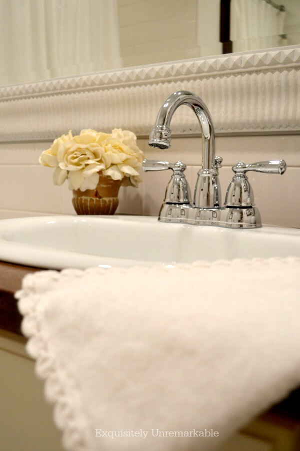 Bathroom vanity with flowers and towel near sink