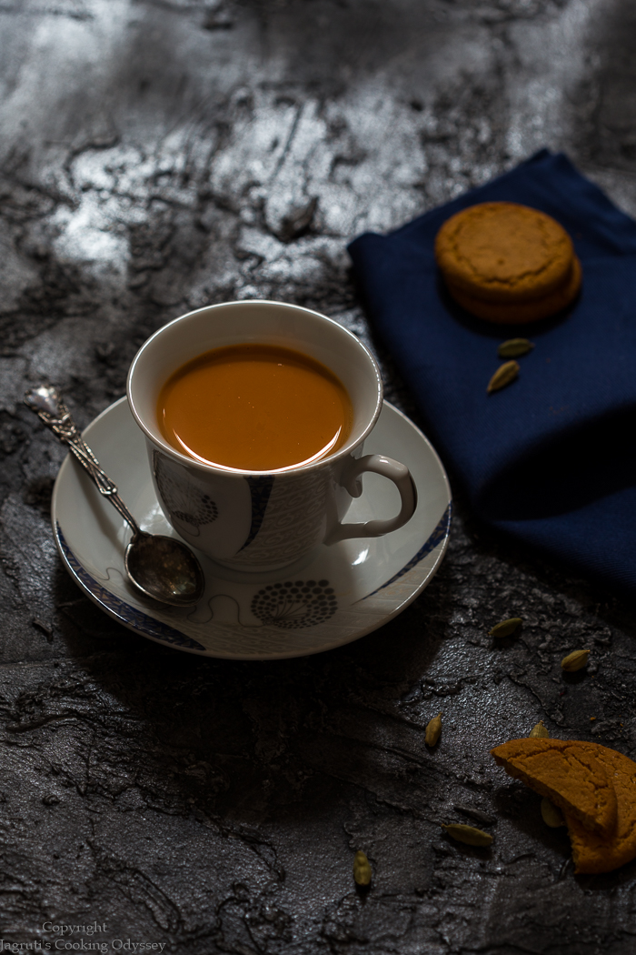 indian cardamom chai tea served in a cup saucer on black backboard