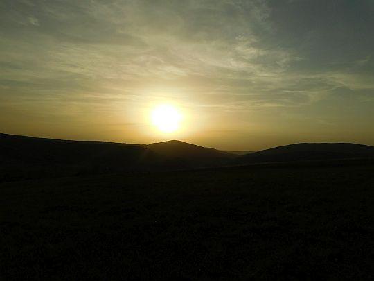 Słońce zachodzące nad wzniesieniem Ostra (687 m n.p.m.).