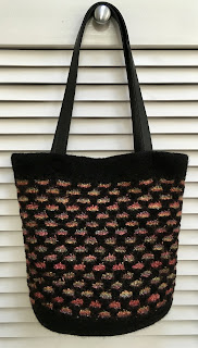 Bag is knitted with rainbow colors and black and fulled