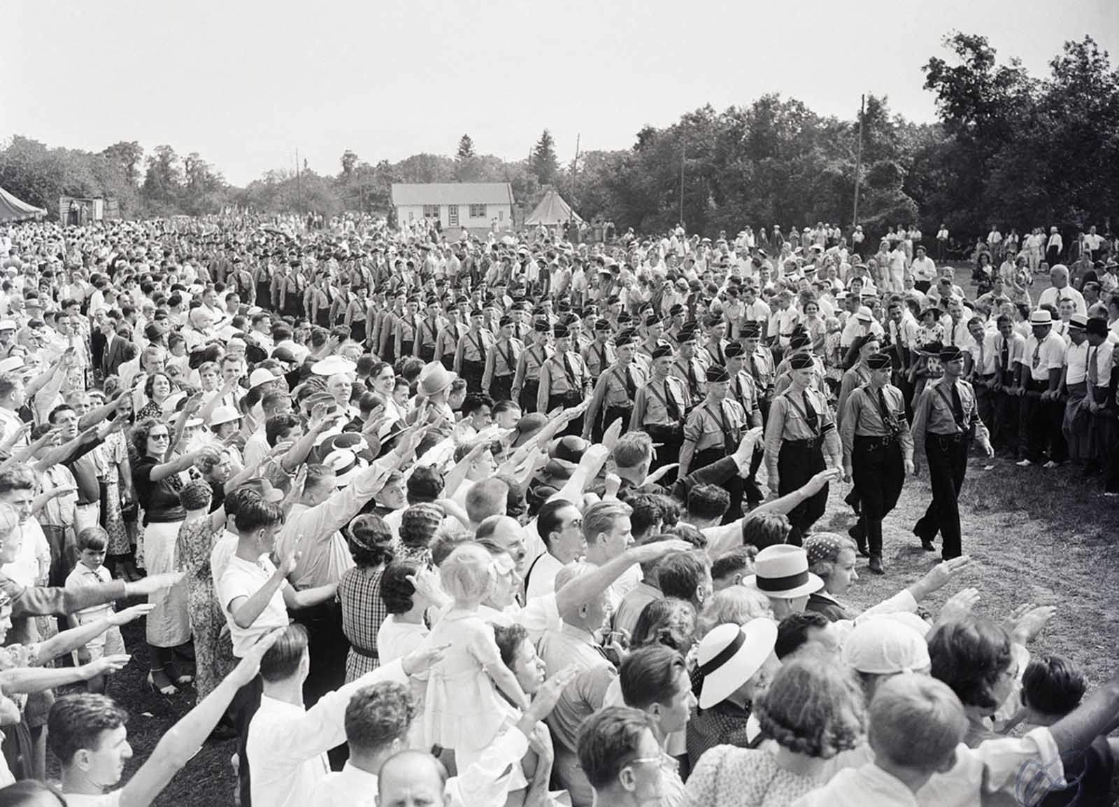 Hundreds of German Americans give the Nazi salute to young men marching in Nazi uniforms. The event was a German Day celebration sponsored by German American Bund at Camp Sigfried on Long Island.