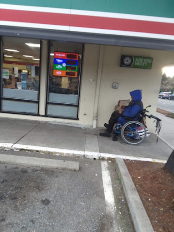 A person in a wheelchair sits outside a 7-11