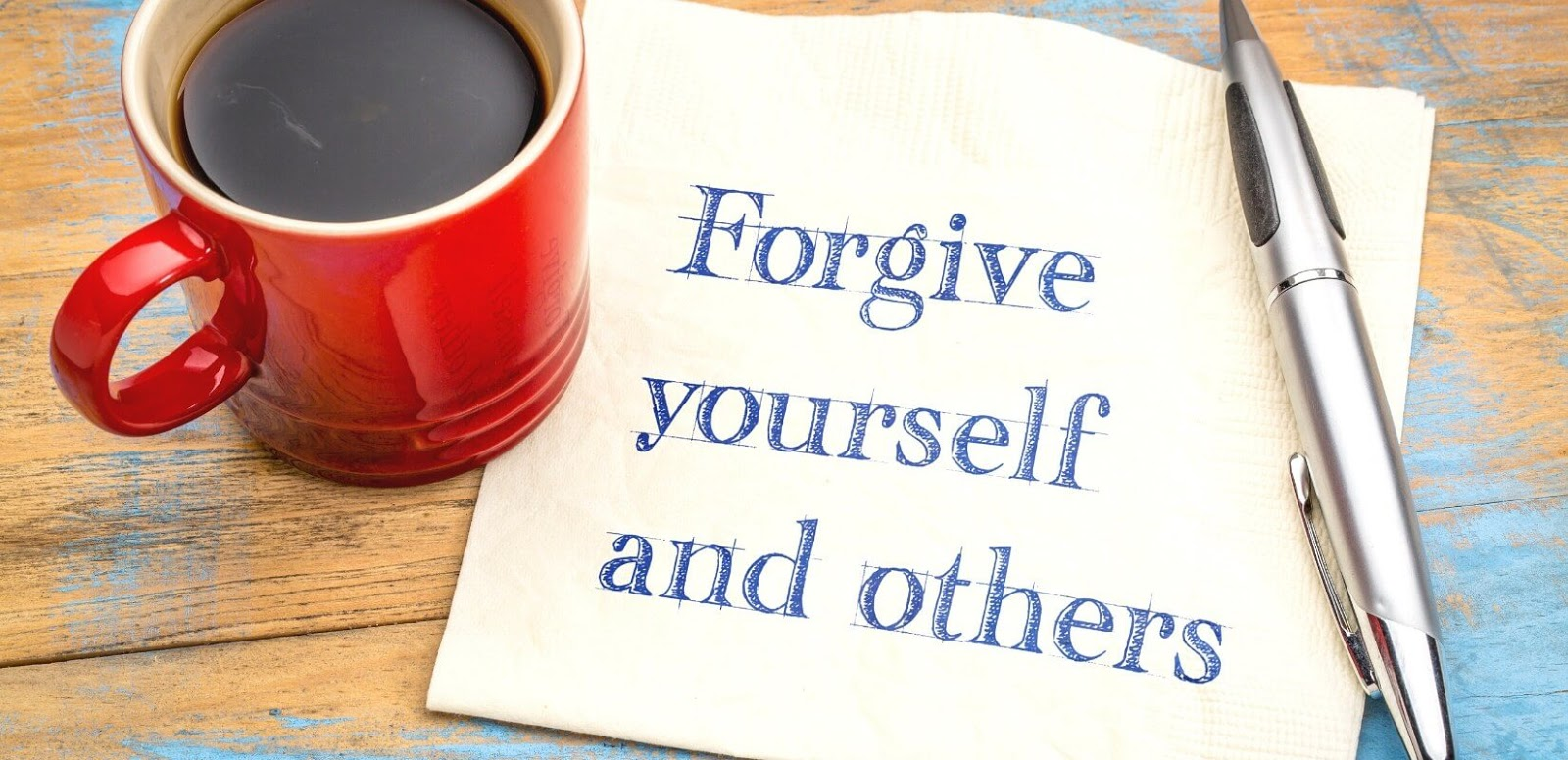 Red coffee cup with paper that reads forgive yourself and others