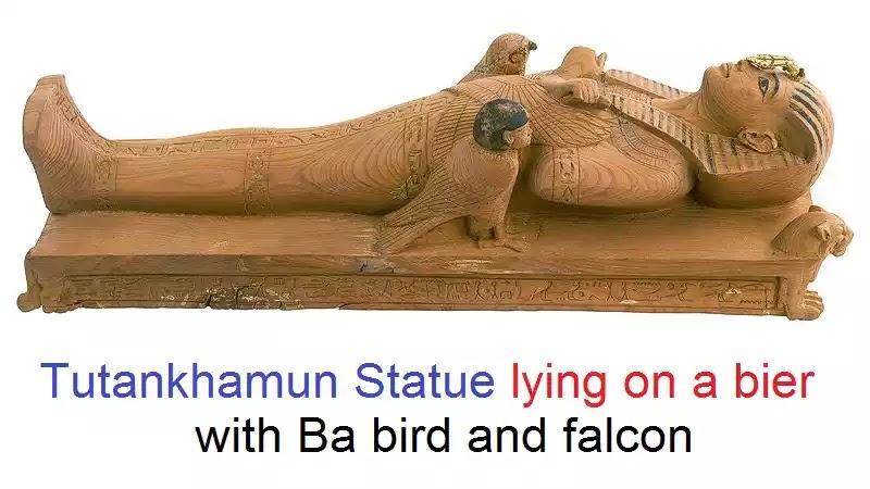 Tutankhamun Statue lying on a bier with Ba bird and falcon