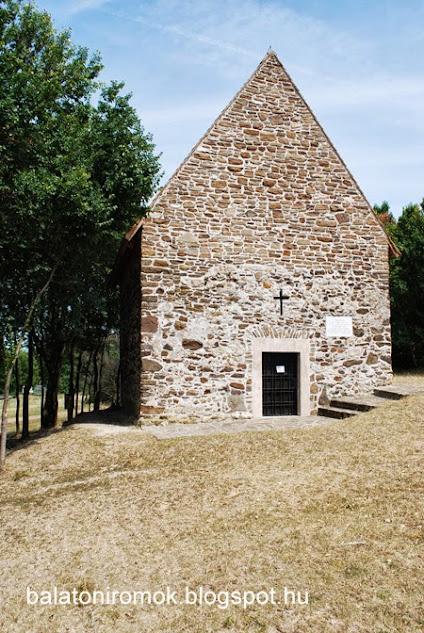 Kis ligetben egy középkori, román stílusú templom, kőből rakott fallal, ajtónyílással.