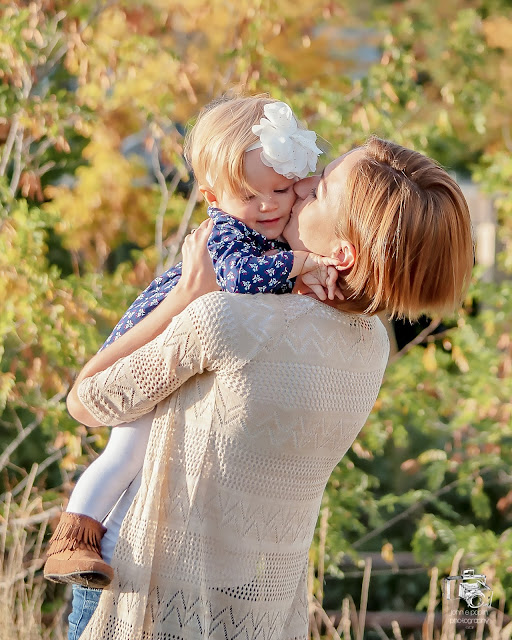 A young mom hold her daughter up in the afternoon sunlight for a family photo session in colorado