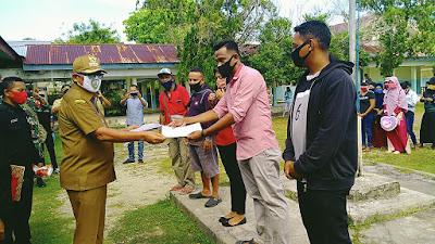 Bupati Malra M. Thaher Hanubun menyerahkan surat keterangan bebas karantina kepada perwakilan pelaku perjalanan
