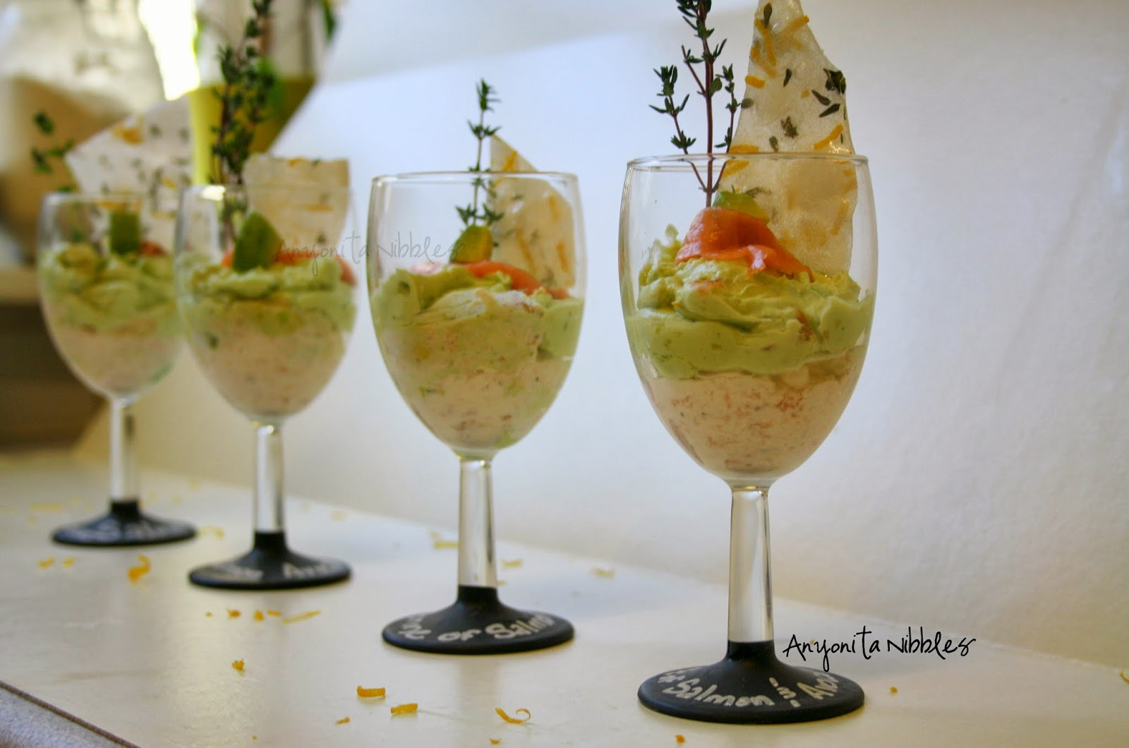 Wine glasses of gsmoked salmon mousse with avocado guacamole