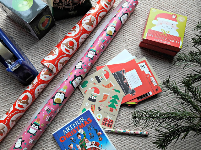 "A photo of a beige textured carpet with a number of Christmas items arranged on it.  From left: a blue Sellotape dispenser, a red roll of Christmas wrapping paper, a pink roll of Christmas wrapping paper, a DVD case for the film ""Arthur Christmas"", a pen, a selection of Christmas cards, a box containing more Christmas cards and the branches of a real Christmas tree"