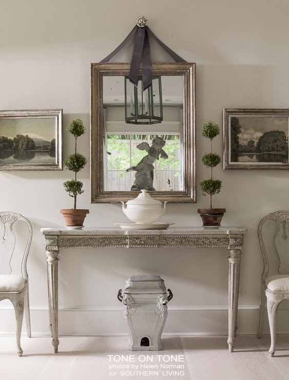 Another stunning vignette with topiaries flanking an antique mirror.