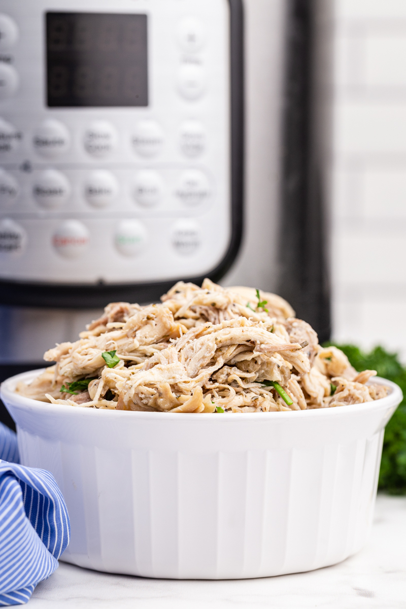 Instant Pot Shredded Chicken in a white bowl with the Instant Pot in the background.