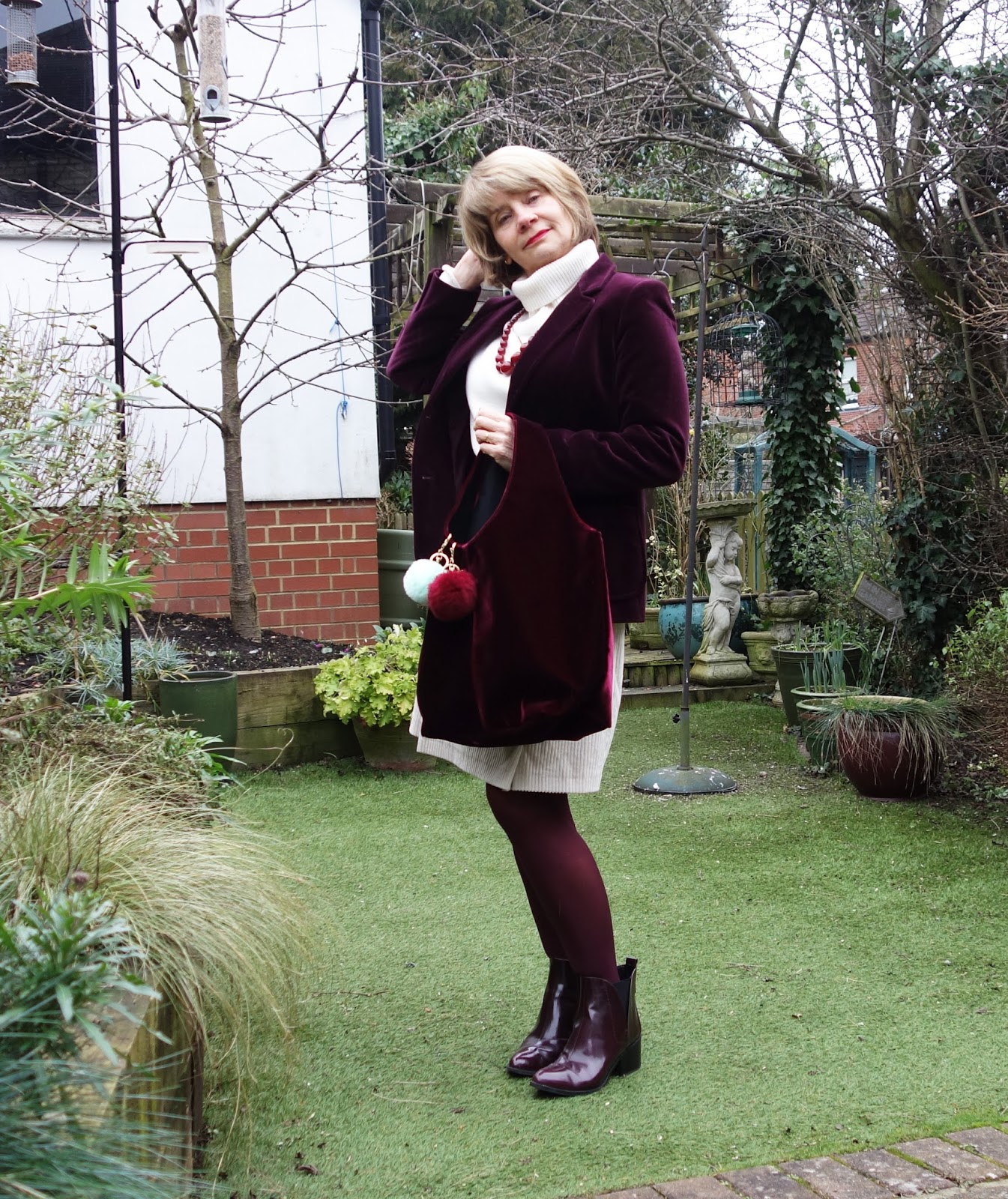Burgundy velvet jacket styled with cream skirt and jumper and burgundy accessories