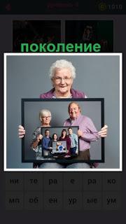 пожилая женщина держит фото с разными поколениям своей семьи