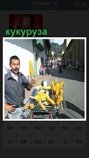 на улице с прилавка продавец продает кукурузу, всем прделагает