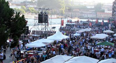Muitas pessoas, barracas e caixas de som na Ribeira do Porto