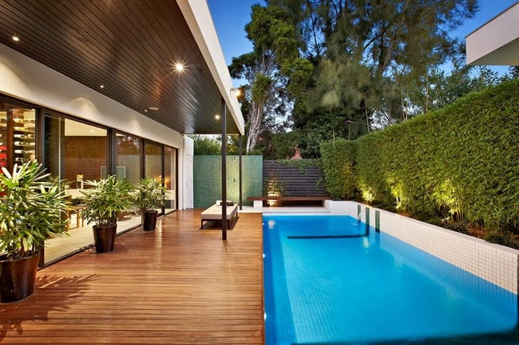 Glass walls and wooden deck in Beautiful modern backyard by Cos Design