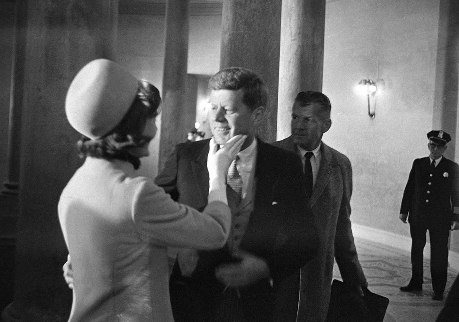 Mrs. Jacqueline Kennedy has a chuck under the chin for her husband moments after he became president, on January 20, 1961. This exclusive picture by AP photographer Henry Burroughs was taken in the rotunda of the Capitol just after President John F. Kennedy left the inaugural stand.