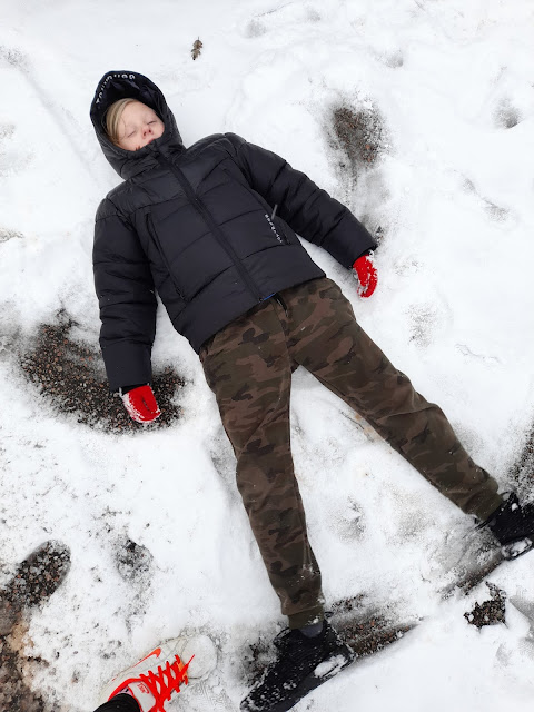 A, a white boy of 10 years is laying on snow covered ground making a snow angel weaing green army joggers and a black puffer coat