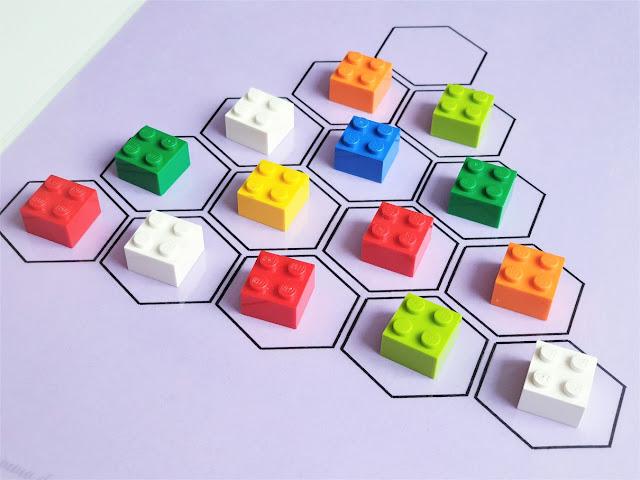 na zdjęciu plansza do gry w trójkątną wersję samotnika. Plansza jest w kolorze fioletowym z piętnastoma polami ułożonymi w kształt trójkąta, na czternastu polach leżą kolorowe klocki lego, jedno pole na wierzchołku planszy jest puste