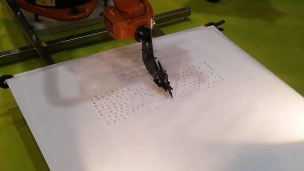 Il robot Kuka scrive qualcosa su un foglio di carta